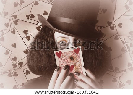 Beautiful retro female magician holding burnt playing card in mysterious style. Act of magic in play - stock photo