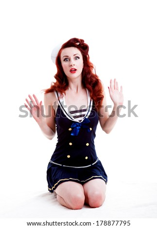 Beautiful retro pin-up girl in a blue and white sailor style outfit looking surprised - stock photo