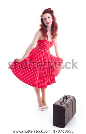 Beautiful retro pin-up girl with red polka dot dress and suitcase  - stock photo