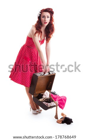 Beautiful retro pin-up girl with red polka dot dress and suitcase with clothes falling out, a look of surprise on her face - stock photo