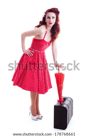 Beautiful retro pin-up girl with red polka dot dress, leaning on her suitcase with an umbrella - stock photo