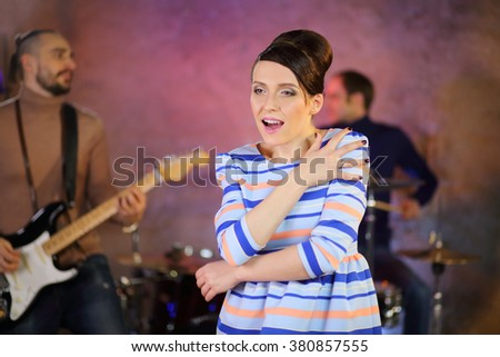 Beautiful retro singer sings a song with feeling near musicians - stock photo