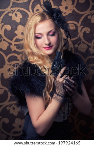 beautiful retro woman holding a revolver - stock photo