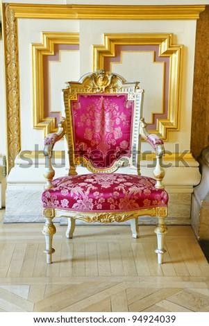 Beautiful rich and luxurious old vintage antique pink silk chair with gold frame showing the wears and tears of years of service. - stock photo