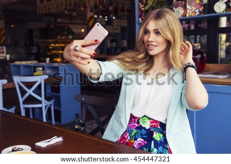 Beautiful rich casual blonde stylish fashion business woman with a phone in her hand make selfie in blue jacket and colorful skirt at the cafe table. European cafe on a background