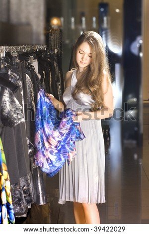 beautiful rich woman chooses a dress in a boutique
