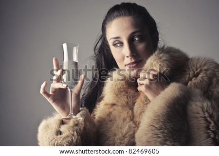 Beautiful rich woman holding a glass of champagne - stock photo