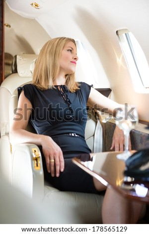 Beautiful rich woman looking through window in private jet - stock photo