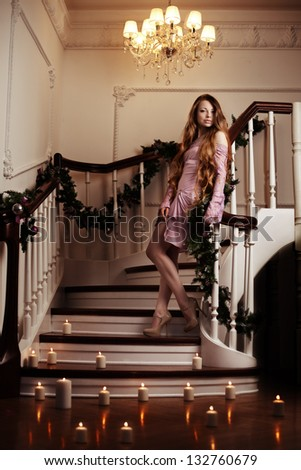 Beautiful rich woman on staircase with a candle - stock photo