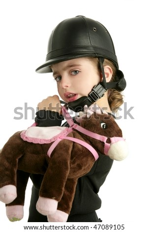 Beautiful riding cap little girl hug a toy horse isolated on white