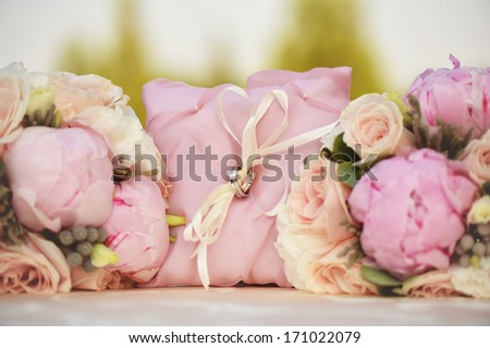 Beautiful ring bearer sorrounded by peonies - stock photo