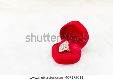 Beautiful ring in velvet red box on white carpet background, Valentine's day, love concept, marry me - stock photo