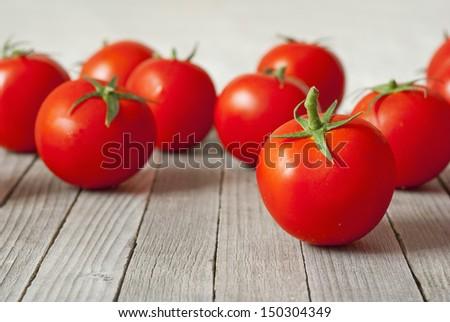 beautiful ripe tomatoes on wood surface - stock photo
