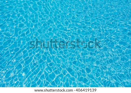 Beautiful rippled water in swimming pool with sun reflection - stock photo
