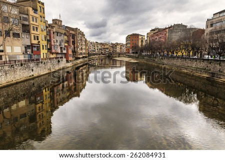 Beautiful river cityscape scene with many buildings reflected on it on a mirror effect and old houses in this famous city landmark in Girona, Catalonia.