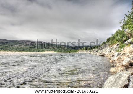 Beautiful river in mountain valley with stone shore