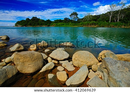 Beautiful river landscape from Costa Rica. River Rio Baru in the tropic forest. Stones in the river. Trees above the river. Summer river with blue sky. Typical landscape in the tropic forest.  - stock photo