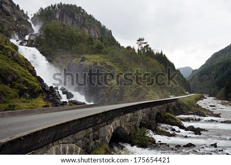beautiful road and old stone bridge above waterfall in Norway - stock photo