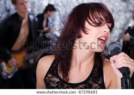 Beautiful rock singer and her team - stock photo
