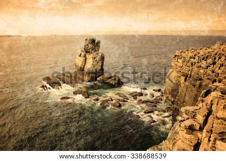 Beautiful rocks in water. Atlantic ocean coast near Peniche (Portugal).  Retro aged photo with scratches. - stock photo