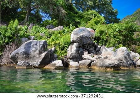 Beautiful rocky coast of the volcanic caldera Lake Coatepeque in Salvador - stock photo