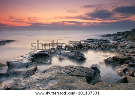 Beautiful rocky sea beach at sunset
