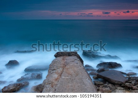 Beautiful rocky sea beach with broken pier at the sunset