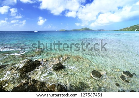 Beautiful rocky shoreline with clear blue waters and a boat traveling to the harbor of Isla Culebra in Puerto Rico - stock photo