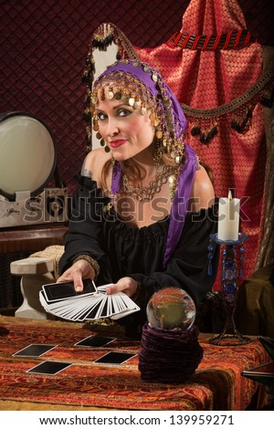 Beautiful Roma woman with crystal ball and tarot cards - stock photo
