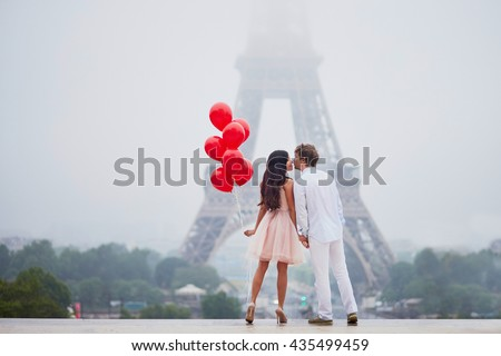 Beautiful romantic couple in love with bunch of red balloons together near the Eiffel tower in Paris on a cloudy and foggy rainy day - stock photo