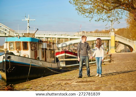 Beautiful romantic couple in Paris walking by the Seine - stock photo