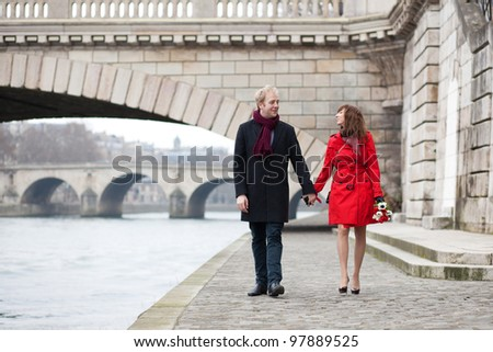 Beautiful romantic couple on a Parisian embankment at spring or winter - stock photo