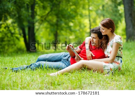 Beautiful romantic couple with tablet pc at summer green park - stock photo