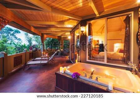 Beautiful Romantic Deck on Tropical Home with Bathtub, Candles, and Flowers at Sunset  - stock photo