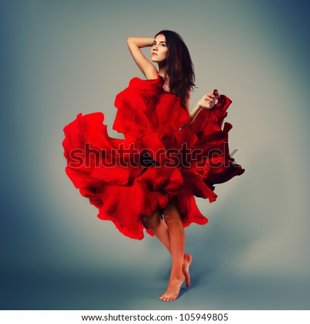 beautiful romantic fashion girl in red flower dress with long brown hair barefoot, full length studio portrait - stock photo