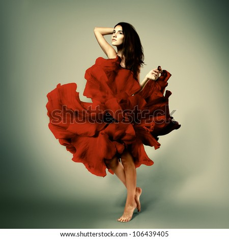 beautiful romantic girl in red flower dress with long broun hair barefoot, full length studio portrait - stock photo