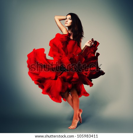 beautiful romantic girl in red flower dress with long brown hair barefoot, full length studio portrait - stock photo