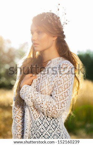 Beautiful romantic girl outdoors. Attractive young girl in a summer field in autumn at sunset. - stock photo