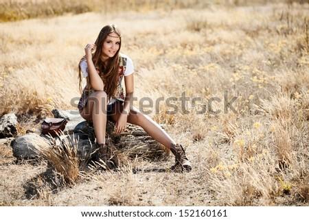 Beautiful romantic girl outdoors. Beautiful teenage girl sitting on a tree stump in the field in sun light.  - stock photo