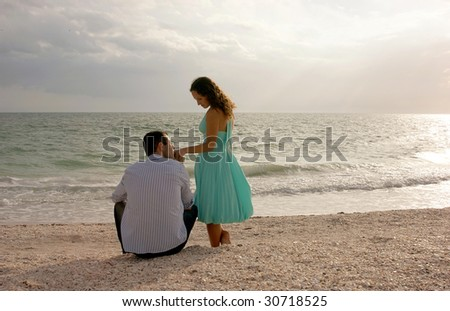beautiful romantic image of couple on beach in the gulf of mexico looking at each other with the man kissing womans hand.  from behind with the ocean in front of them as the sun begins to set. - stock photo