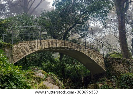 Beautiful romantic stone bridge in mystical green forest / park / garden with spooky trees, during foggy day. Pena Palace Sintra - stock photo