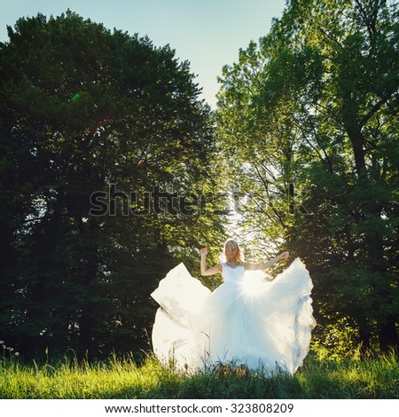 beautiful romantic stylish blonde bride in white dress dancing in the forest in the sun