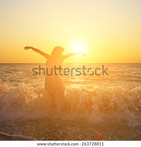 Beautiful romantic woman at the seaside at sunset - stock photo