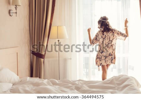 Beautiful romantic woman / girl brunette lying on the bed in her room at home. - stock photo
