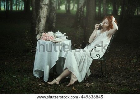 Beautiful romantic woman having tea in the woods. Surreal and dreamy