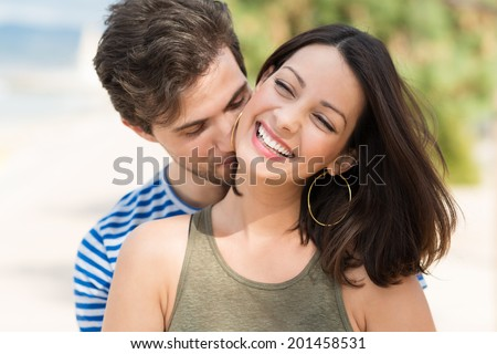 Beautiful romantic young couple on a beach with the young man nuzzling the neck of his girlfriend or wife as she laughs in enjoyment - stock photo