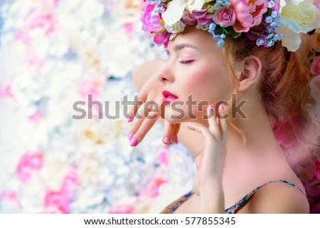 Đẹp người phụ nữ trẻ tuổi lãng mạn trong một vòng hoa đặt ra trên một nền tảng của hoa hồng.  Cảm hứng của mùa xuân và mùa hè.  Nước hoa, mỹ phẩm khái niệm.