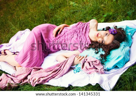 beautiful romantic young woman in pink dress lie in garden on pillow summer day - stock photo