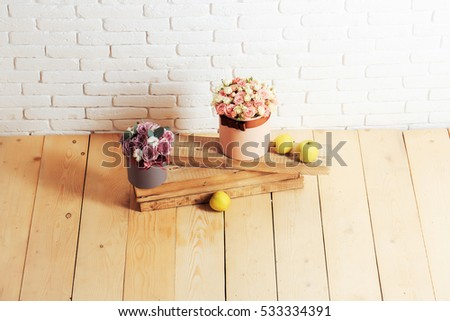 beautiful rose flowers bouquet in boxes pink and violet colors near green apples on wooden planks on wood floor on white brick wall background