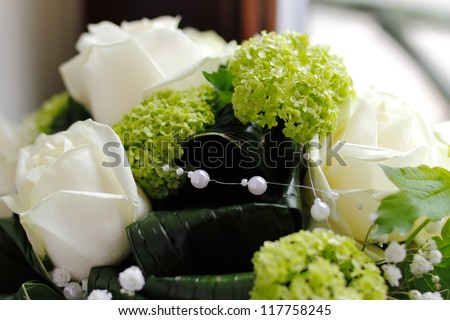 Beautiful rose with white color purity with white perls with a green background, landscape oriented photo, focused to center - stock photo